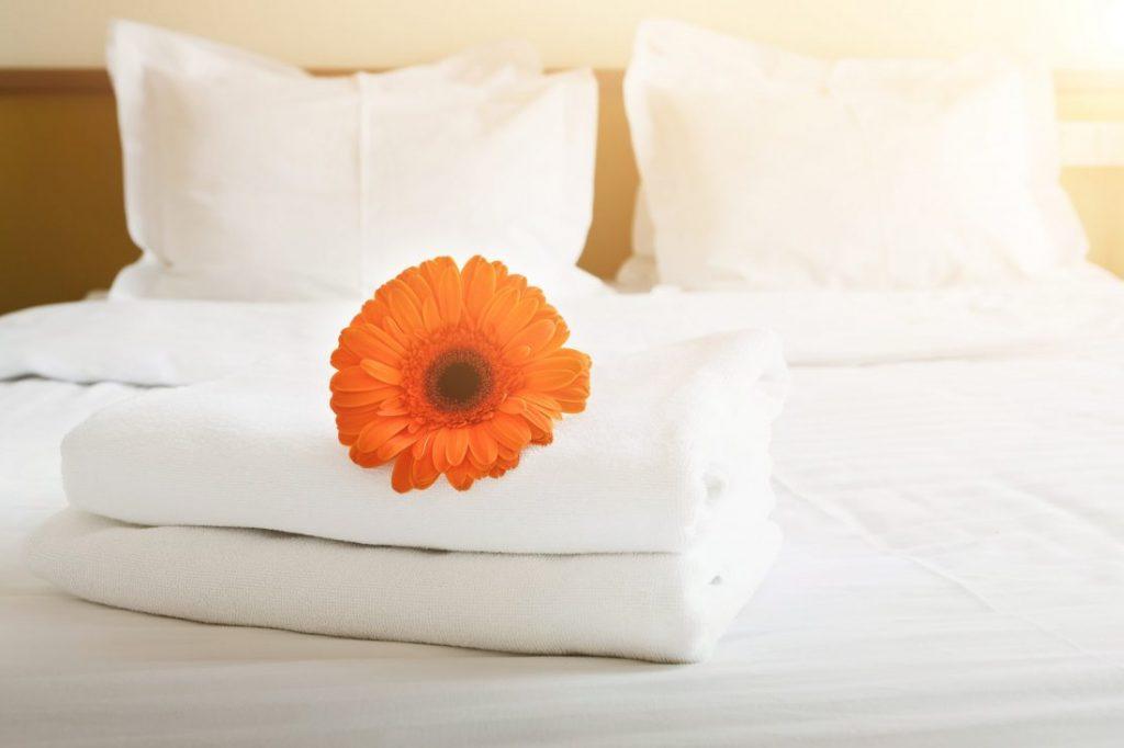 평택 송화지구 아파트 단지배치Stack of towels and flower on bed in hotel room